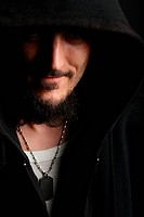 Young man in black hood smiles in shadow