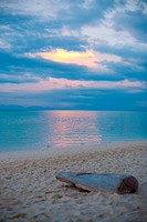 A dreamy scene of a lone piece of driftwood on the beach at sunset in Koh Lipe Ko Lipeh Thailand.