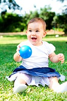 an adorable baby girl playing with blue ball in park