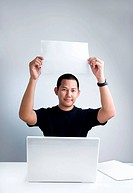 Man holding blank white paper at his desk