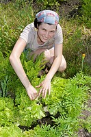 Smiling gardener in vegetable garden. Woman is working hard.