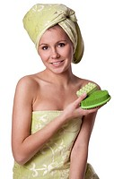 Beautiful girl in a green towel keeps bath means Hygiene on white background. Girl after shower