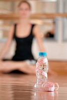Young girl in lotus pose. Bottle with measuring tape on foreground. Blured background