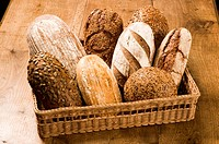 Basketful of various types of brown bread on a wooden table