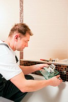 Plumber installing a mixer tap in a bathroom, he is sitting in the bathtub, focus on eyes of the man!