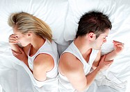Sad and angry couple lying in bed separately after having an argument. Marriage trouble