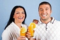Happy laughing young couple holding glassess with orange juice,concept of healthy lifestyle on blue background