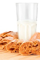 Glass of milk and fresh homemade bread on wooden table. Shallow depth of field