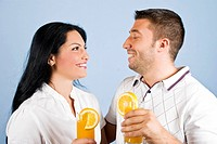 Healthy couple holding glasses with fresh orange juice,standing face to face looking at each other and laughing together