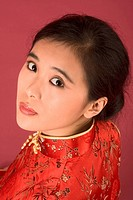 Portrait of young beautiful Chinese female in traditional clothes cheongsam