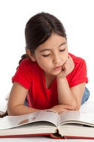 Eight year old girl reading a book on white background