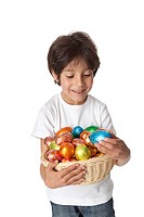 Little boy with a basket of chocolate Easter eggs on white background