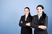 Two business women standing one close to each other with hands crossed and smiling for you,copy space for text message in left part of image