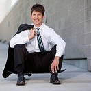 Businessman sitting on a skateboard outdoors.