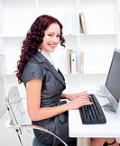 Beautiful smiling businesswoman working in office with a computer