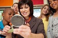 A teacher is showing a group of students in a classroom a leaf from a plant through a magnifying glass.
