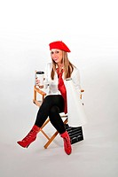 pretty young movie director in a red beret with a cup of coffee in one hand and a megaphone in the other