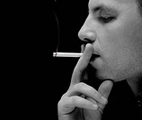 young man smokes a cigarette on a dark background