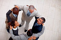 Top view of a group of business people standing with their hands on eachothers shoulder
