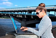 business woman with the laptop on city quay