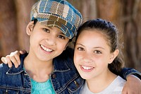 Portrait of Smiling Tween Girls leaning on each other outdoors.