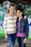Portrait of Smiling Tween Girls arm in arm outdoors in a park.