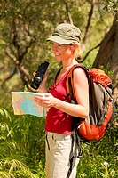 young blonde woman hiking and holding binoculars and map.