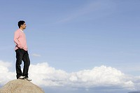 Man Standing on Rock in Front of Blue Sky and Clouds Looking into Distance