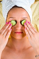 Beautiful young woman holding slices cucumber on her eyes at spa center