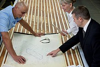 Three people look over blueprints in a factory.