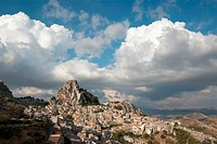 rock of Caltabellotta village in Sicily, in the background dramatic sky with big clouds