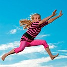 photo of a jumping kid in the air in front of a summer sky