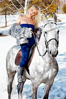 outdoor portrait of beautiful blonde girl with pale horse in sunny winter forest