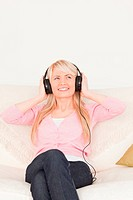 Beautiful woman listening to music on her headphones while sitting on a sofa in the living room