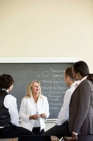 Businesswoman stands at a chalkboard while conducting a team meeting.