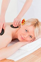 Attractive woman receiving a massage with hot stones in a Spa centre