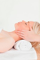 Cute blonde woman enjoying her treatment while lying down in a Spa centre
