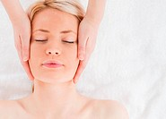 Delighted blond_haired woman getting a massage on her face in a Spa centre