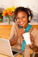 A young woman sitting in a cafe and drinking a beverage. She has a laptop open on the table in front of her and she is wearing headphones draped aroun...