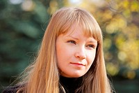 Outdoor portrait of young blonde woman in autumn sunlight