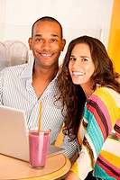 Young couple smile towards the camera while seated at a laptop and smoothie. Vertical shot.