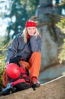 Active young woman rock climbing sitting backback with rope