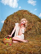 portrait of beautiful blonde country girl posing on yellow hay with basket of apples