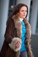 fashion woman in fur coat walking on the street