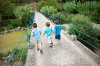 three boys crossing an old bridge on the country, Ludiente, Castellón, Spain