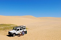 Two men sitting in front of a Landrover Defender off-road vehicle in the dunes of the Namib Naukluft National Park, part of the Namibian Skeleton Coas...