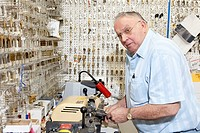 Senior locksmith looking away while making key in store