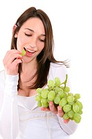 A young, pretty, and healthy woman eating grapes
