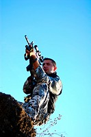 Soldier in camouflage aiming with his rifle outdoor