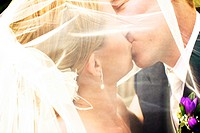 kissing through the veil - close up of bride and groom